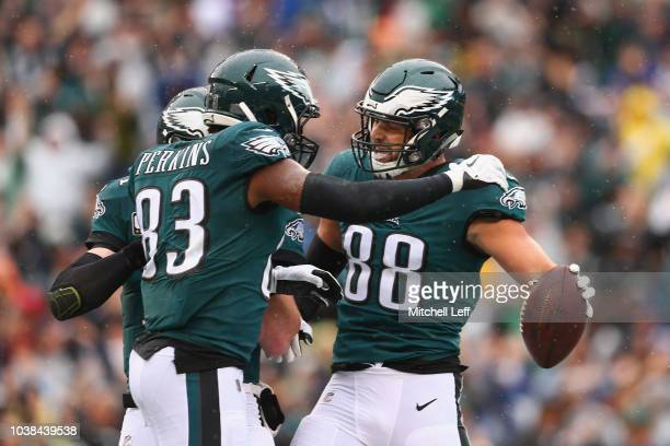Tight end Dallas Goedert of the Philadelphia Eagles celebrates with teammates tight end Josh Perkins and quarterback Carson Wentz after Goedert made...