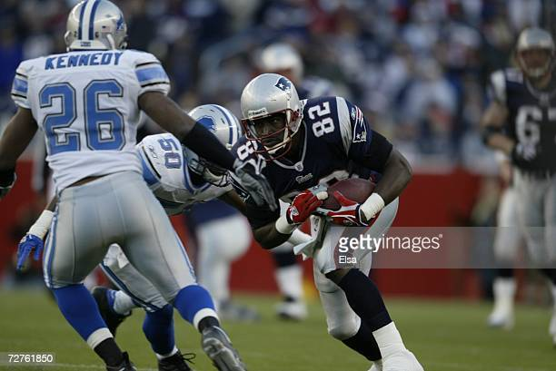 Tight end Daniel Graham of the New England Patriots carries the ball against safety Kenoy Kennedy and linebacker Ernie Sims of the Detroit Lions on...