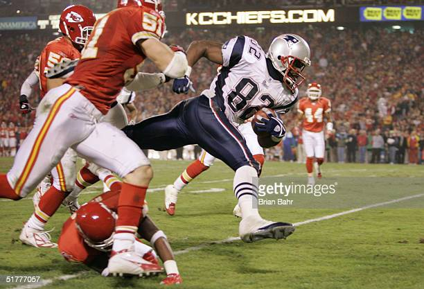 Tight end Daniel Graham of the New England Patriots stretches for more yardage on a 48yard gain against Shaunard Harts and Scott Fujita of the Kansas...