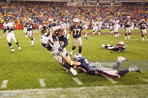 Tight End Daniel Wilcox of the Baltimore Ravens is tackled by Linebacker Mike Vrabel of the New England Patriots at Gillette Stadium on November 28...