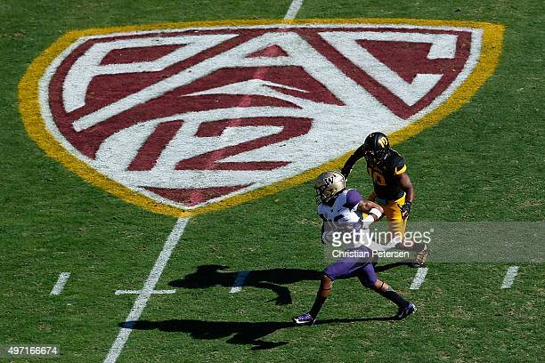 Tight end Darrell Daniels of the Washington Huskies runs with the football after a reception past defensive back Kweishi Brown of the Arizona State...