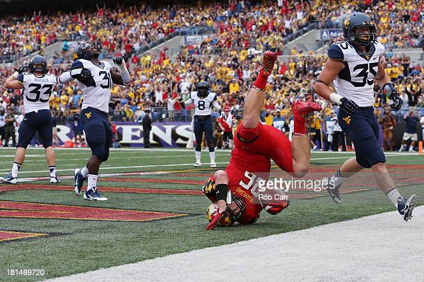 Tight end Dave Stinebaugh of the Maryland Terrapins catches a touchdown pass in front of linebacker Nick Kwiatkoski of the West Virginia Mountaineers...