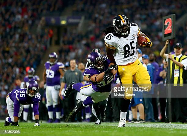 Tight end David Johnson of the Pittsburgh Steelers is tackled by outside linebacker Chad Greenway of the Minnesota Vikings during the NFL...