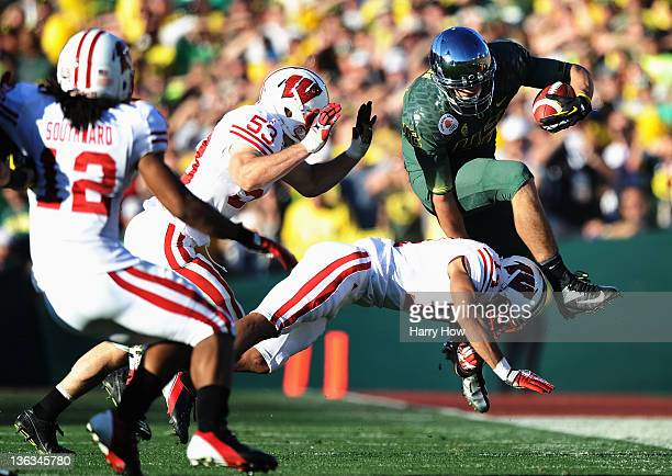 Tight end David Paulson of the Oregon Ducks leaps over a Wisconsin Badgers defender in the second quarter for a 10yard gain at the 98th Rose Bowl...