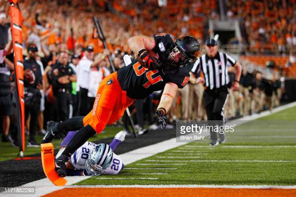 Tight end Dayton Metcalf of the Oklahoma State Cowboys helicopters into the pilon for a 14-yard touchdown on a catch and run against defensive back...