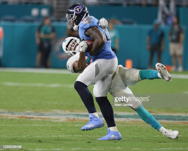 Tight End Delanie Walker of the Tennessee Titans suffers a severe ankle injury as he is tackled by Safety TJ McDonald of the Miami Dolphins at Hard...