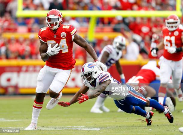 Tight end Demetrius Harris of the Kansas City Chiefs carries the ball after making a catch as defensive back Leonard Johnson of the Buffalo Bills...