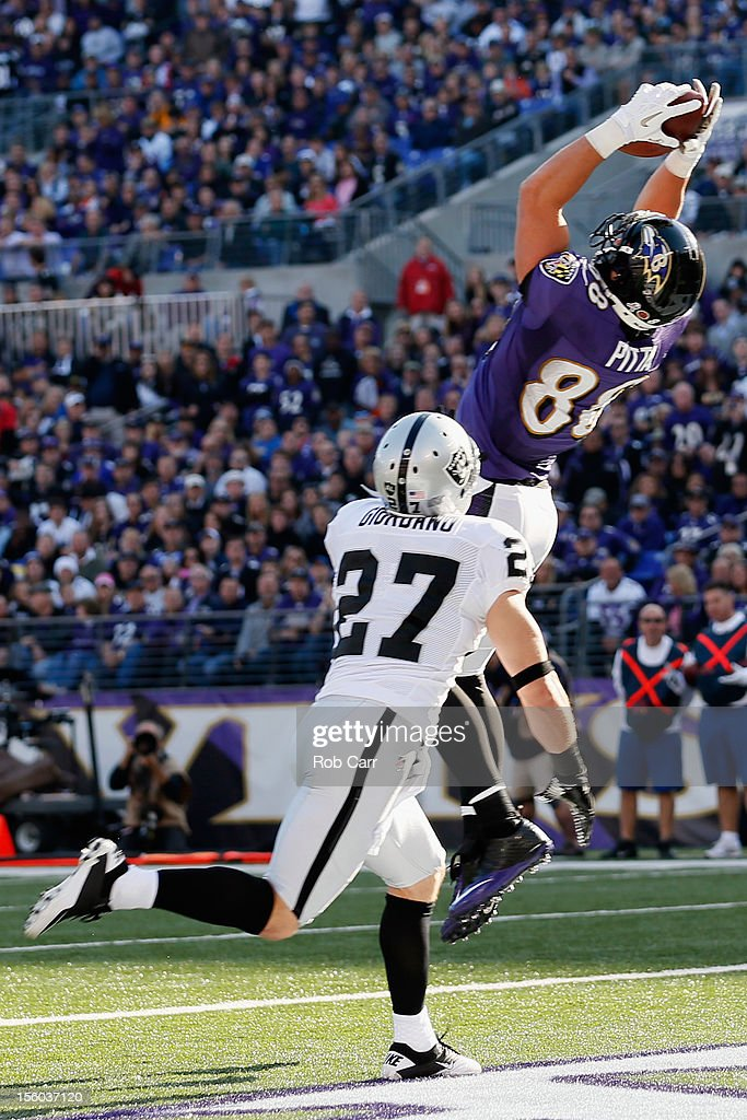 Tight end Dennis Pitta #88 of the Baltimore Ravens catches a touchdown pass in front of free safety Matt Giordano #27 of the Oakland Raiders during the first half at M&T Bank Stadium on November 11, 2012 in Baltimore, Maryland.