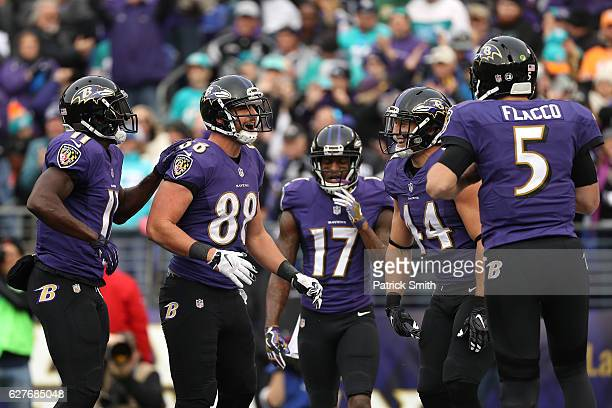 Tight end Dennis Pitta of the Baltimore Ravens celebrates with teammates wide receiver Kamar Aiken wide receiver Mike Wallace fullback Kyle Juszczyk...