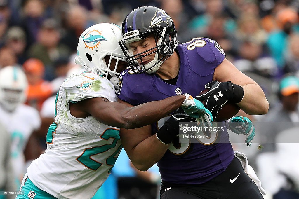 Tight end Dennis Pitta #88 of the Baltimore Ravens is tackled by strong safety Isa Abdul-Quddus #24 of the Miami Dolphins in the first quarter at M&T Bank Stadium on December 4, 2016 in Baltimore, Maryland.