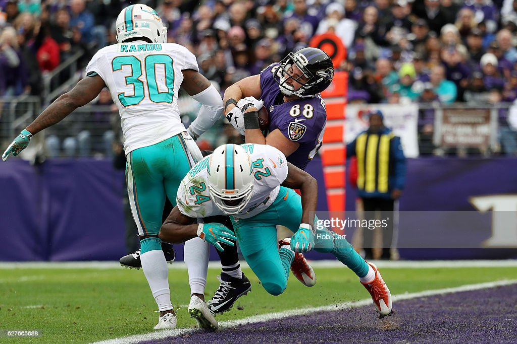 Tight end Dennis Pitta #88 of the Baltimore Ravens scores a first quarter touchdown against strong safety Isa Abdul-Quddus #24 and free safety Bacarri Rambo #30 of the Miami Dolphins at M&T Bank Stadium on December 4, 2016 in Baltimore, Maryland.
