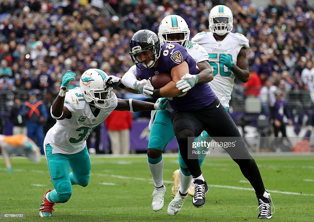 Tight end Dennis Pitta #88 of the Baltimore Ravens scores a second quarter touchdown against free safety Michael Thomas #31, free safety Bacarri Rambo #30 and defensive end Andre Branch #50 of the Miami Dolphins at M&T Bank Stadium on December 4, 2016 in Baltimore, Maryland.