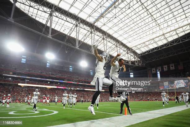 Tight end Derek Carrier of the Oakland Raiders celebrates with Derek Carr after scoring on a two yard touchdown reception against the Arizona...