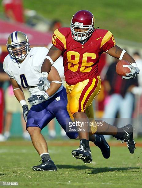 Tight end Dominique Byrd of the USC Trojans breaks for a long gain in front of Scott White of the Washington Huskies at the Los Angeles Coliseum on...