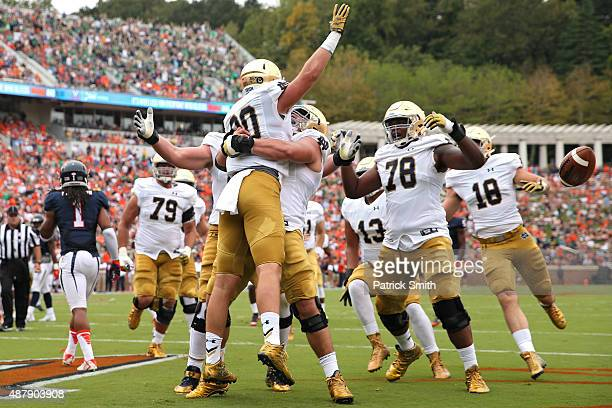 Tight end Durham Smythe of the Notre Dame Fighting Irish celebrates with teammates after scoring a touchdown on a fake field goal attempt in the...