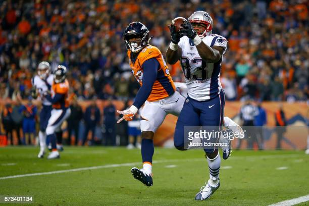 Tight end Dwayne Allen of the New England Patriots catches a pass before scoring a second quarter touchdown under coverage by outside linebacker Von...