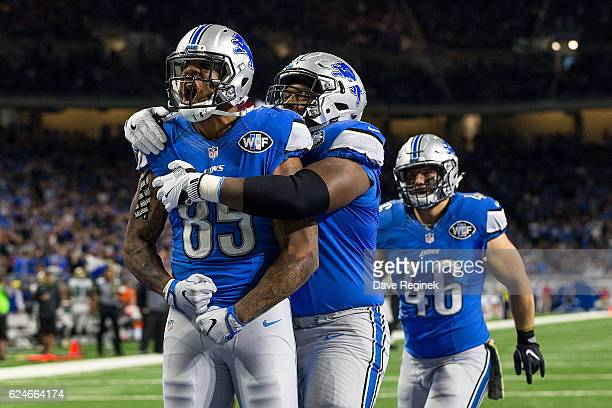 Tight end Eric Ebron of the Detroit Lions celebrates his second half touchdown with teammates Laken Tomlinson and Michael Burton during an NFL game...