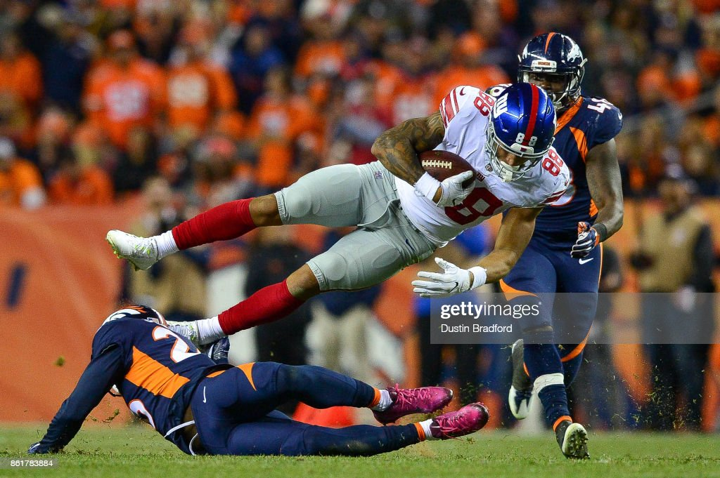 Tight end Evan Engram #88 of the New York Giants flies through the air after being tackled by free safety Darian Stewart #26 of the Denver Broncos at Sports Authority Field at Mile High on October 15, 2017 in Denver, Colorado.