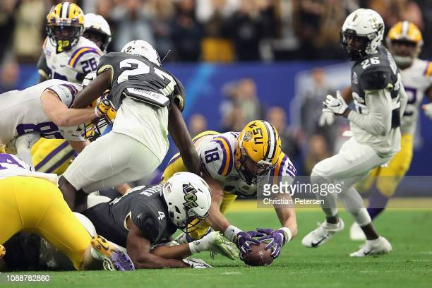Tight end Foster Moreau of the LSU Tigers recovers an onside kick over running back Taj McGowan of the UCF Knights during the fourth quarter of the...