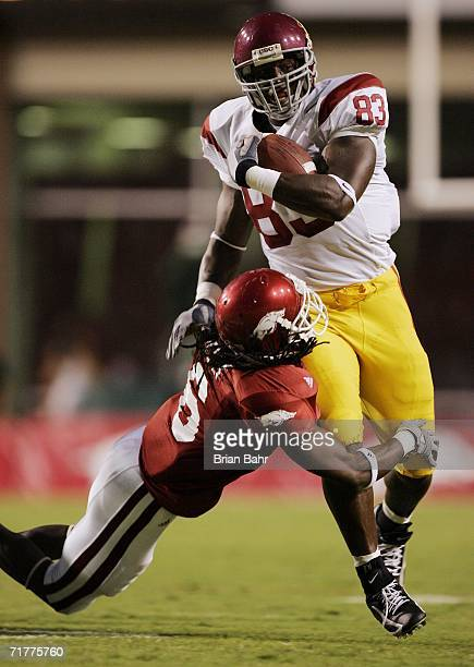 Tight end Fred Davis of the University of Southern California Trojans drags safety Randy Kelly of the Arkansas Razorbacks for a few extra yards on...