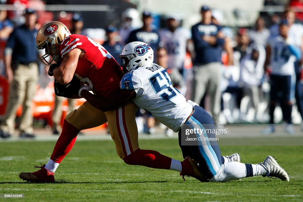 Tight end Garrett Celek #88 of the San Francisco 49ers is tackled by linebacker Jayon Brown #55 of the Tennessee Titans of the San Francisco 49ers is during the first quarter at Levi's Stadium on December 17, 2017 in Santa Clara, California. The San Francisco 49ers defeated the Tennessee Titans 25-23.