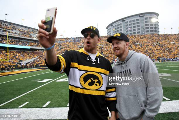 Tight end George Kittle and quarterback CJ Beathard of the San Francisco 49ers take photos on the field during the matchup between their alma mater...