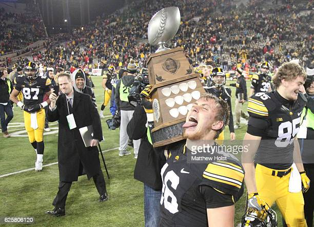 Tight end George Kittle of the Iowa Hawkeyes celebrate with the Heroes Trophy after defeating the Nebraska Cornhuskers on November 25 2016 at Kinnick...