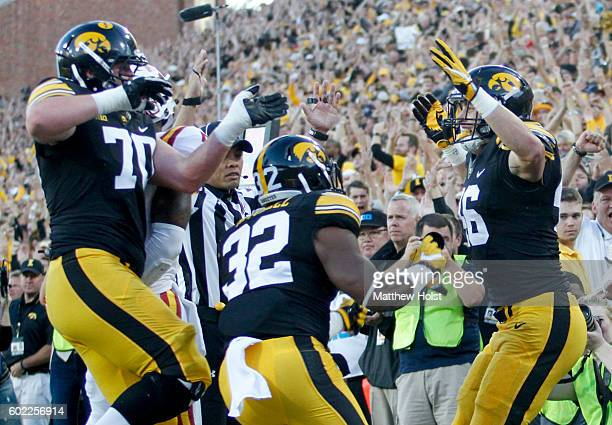Tight end George Kittle of the Iowa Hawkeyes celebrates with offensive lineman Lucas LeGrand and running back Derrick Mitchell after scoring a...