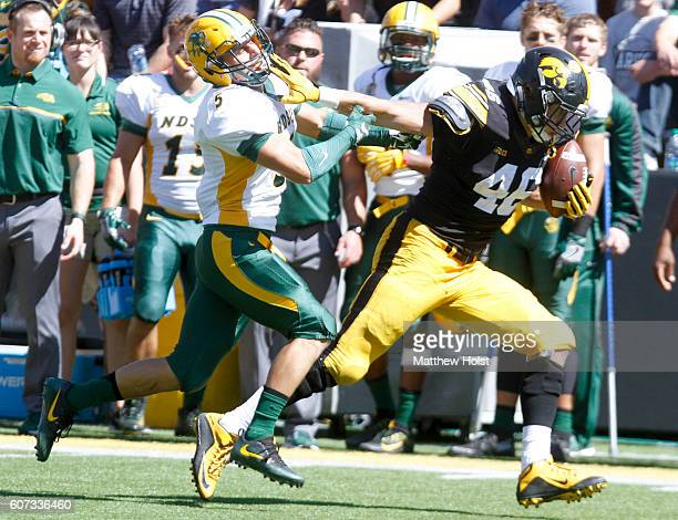 Tight end George Kittle of the Iowa Hawkeyes runs down the field during the third quarter in front of strong safety Robbie Grimsley of the North...