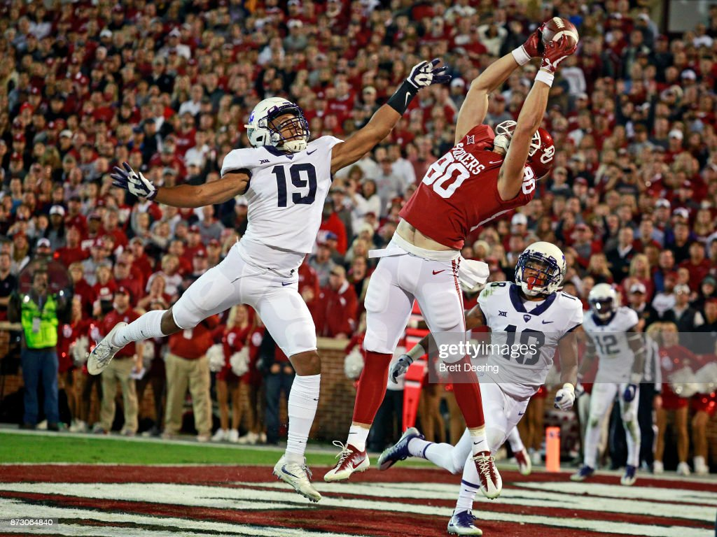 Tight end Grant Calcaterra #80 of the Oklahoma Sooners catches a touchdown pass as linebacker Montrel Wilson #19 of the TCU Horned Frogs defends at Gaylord Family Oklahoma Memorial Stadium on November 11, 2017 in Norman, Oklahoma.