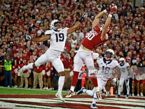 Tight end Grant Calcaterra of the Oklahoma Sooners catches a touchdown pass as linebacker Montrel Wilson of the TCU Horned Frogs defends at Gaylord...