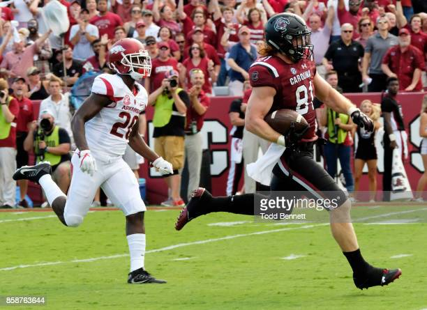 Tight end Hayden Hurst of the South Carolina Gamecocks runs for a touchdown as he's chased by defensive back De'Andre Coley of the Arkansas...