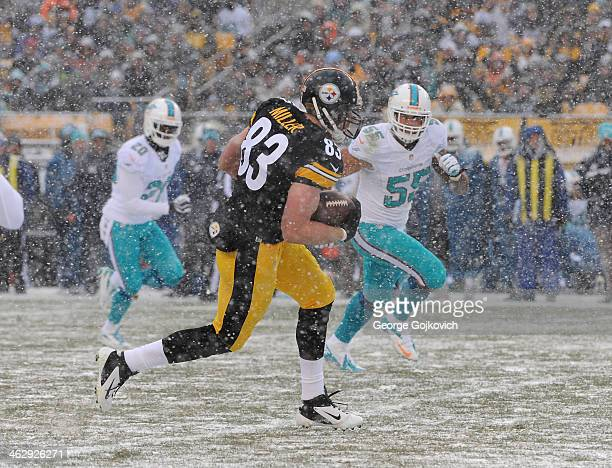 Tight end Heath Miller of the Pittsburgh Steelers is pursued by safety Reshad Jones and linebacker Koa Misi of the Miami Dolphins as snow falls...