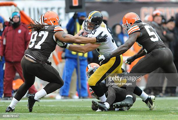Tight end Heath Miller of the Pittsburgh Steelers is tackled by linebackers Jaabal Sheard and Barkevious Mingo of the Cleveland Browns during a game...