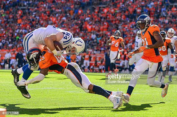 Tight end Jack Doyle of the Indianapolis Colts is stopped after a catch by strong safety TJ Ward of the Denver Broncos at Sports Authority Field at...