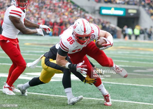 Tight end Jack Stoll of the Nebraska Cornhuskers dives for a touchdown in the first half in front of defensive back Riley Moss of the Iowa Hawkeyes...
