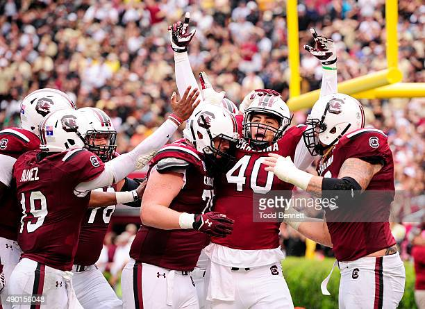Tight end Jacob August of the South Carolina Gamecocks is congratulated by teammates after scoring a touchdown against the University of Central...