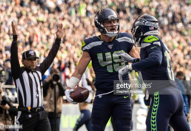 Tight end Jacob Hollister of the Seattle Seahawks and wide receiver Malik Turner celebreate a touchdown during the first half of game against the...
