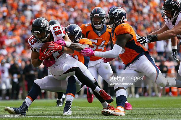 Tight end Jacob Tamme of the Atlanta Falcons is tackled by inside linebacker Todd Davis of the Denver Broncos at Sports Authority Field at Mile High...