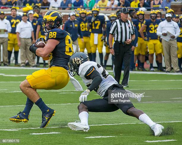 Tight end Jake Butt of the Michigan Wolverines catches the football in front of defensive back TJ Mutcherson of the UCF Knights during a college...