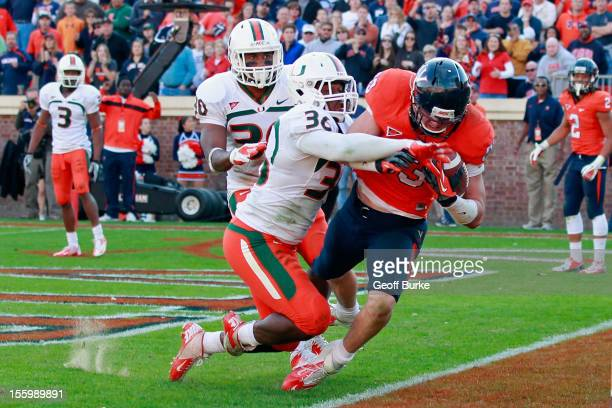 Tight end Jake McGee of the Virginia Cavaliers catches the ball for the game-winning touchdown in the final seconds as linebacker Gionni Paul of the...