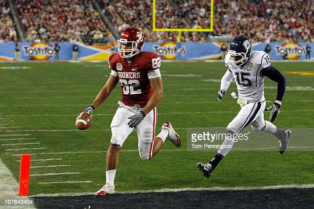 Tight end James Hanna of the Oklahoma Sooners catches a touchdown pass in the first quarter past Jerome Junior of the Connecticut Huskies during the...