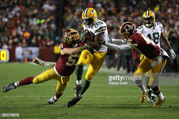 Tight end Jared Cook of the Green Bay Packers carries the ball against inside linebacker Will Compton and cornerback Quinton Dunbar of the Washington...