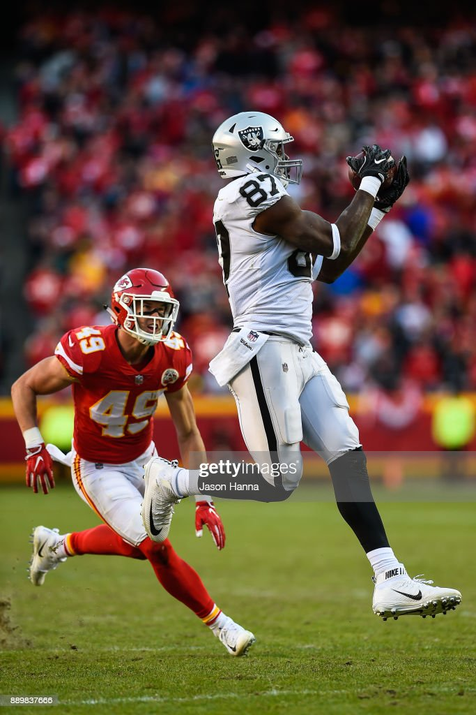 Tight end Jared Cook #87 of the Oakland Raiders hauls in a pass that would lead to a touchdown in front of the coverage of strong safety Daniel Sorensen #49 of the Kansas City Chiefs during the fourth quarter of the game at Arrowhead Stadium on December 10, 2017 in Kansas City, Missouri.