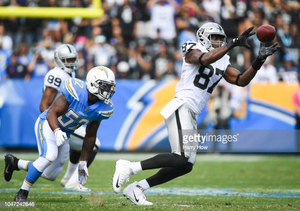 Tight end Jared Cook of the Oakland Raiders makes a catch in front of linebacker Denzel Perryman of the Los Angeles Chargers in the first quarter at...