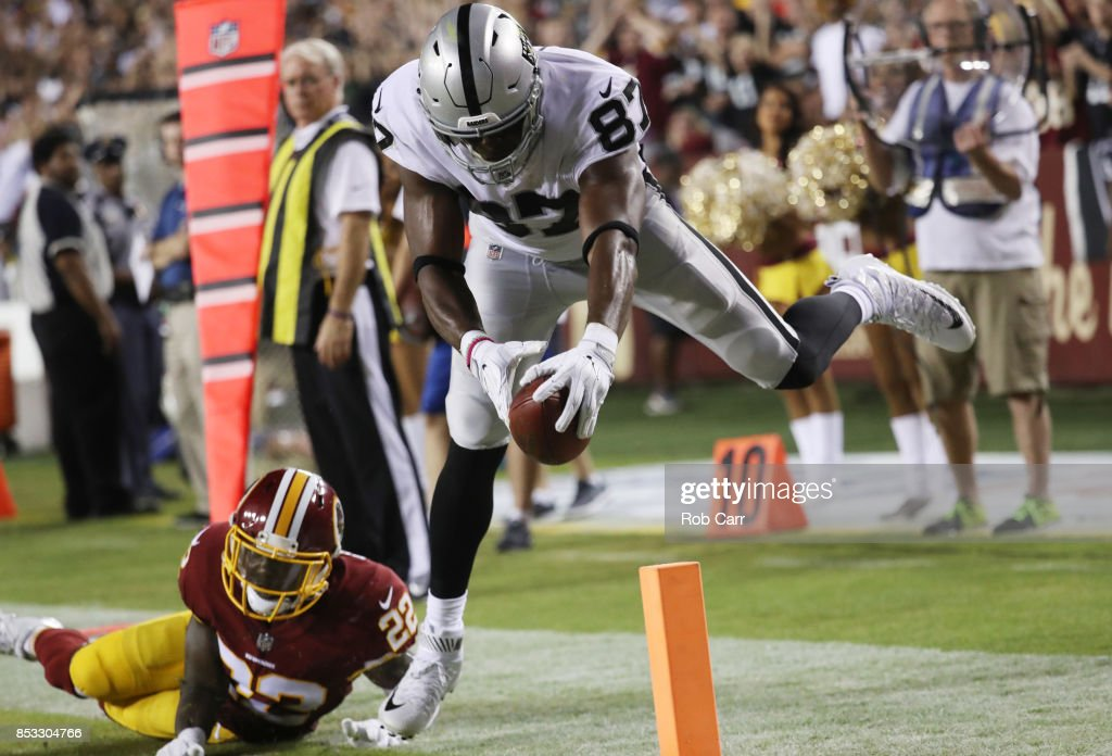 Tight end Jared Cook #87 of the Oakland Raiders scores a touchdown over strong safety Deshazor Everett #22 of the Washington Redskins in the third quarter at FedExField on September 24, 2017 in Landover, Maryland.