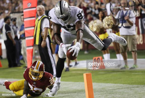 Tight end Jared Cook of the Oakland Raiders scores a touchdown over strong safety Deshazor Everett of the Washington Redskins in the third quarter at...