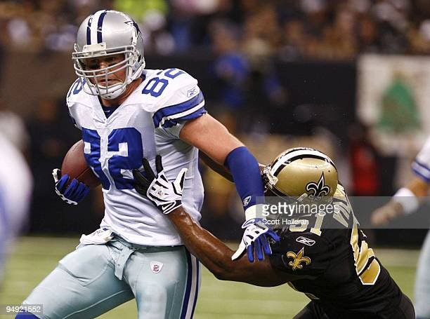 Tight end Jason Witten of the Dallas Cowboys runs with the ball as linebacker Jonathan Vilma of the New Orleans Saints trys to tackle him at the...