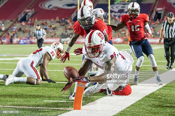 Tight end Jaylen Samuels of the North Carolina State Wolfpack leaps for the end zone in front of cornerback Jeremy Reaves of the South Alabama...