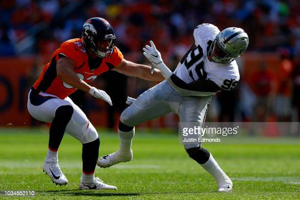 Tight end Jeff Heuerman of the Denver Broncos blocks defensive end Arden Key of the Oakland Raiders during a game at Broncos Stadium at Mile High on...